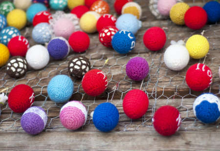 Decorative multi-colored easter eggs hanging on a wooden background wall. Selective focus, shallow FOF photo