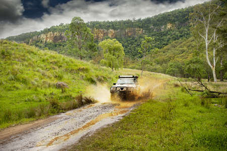 a 4x4 creates a mudsplash as it travels along a muddy country road (all branding removed)