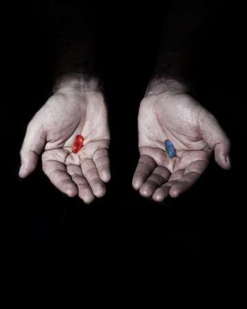 pills in hand: momento cl�sico de la Matriz, elija la pastilla roja o azul Foto de archivo