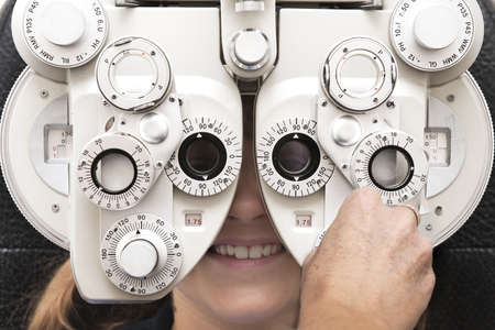 exams: an optometrist adjusts the dials on the phoropter during an eye test Stock Photo