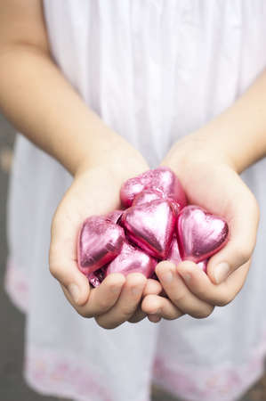 a girl holds pink foiled chocolate hearts in hands Stock Photo - 12338345