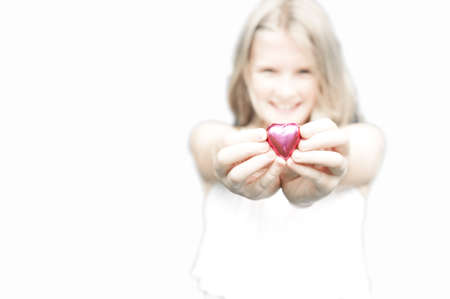 a pink foiled chocolate heart is held forward, a young pretty blonde girl in the background. Copy space. Stock Photo - 12338346