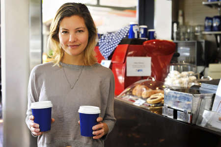 a young woman with takeaway coffees  This model has a lovely natural look  photo