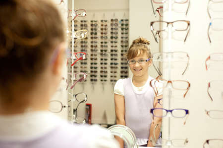 a young girl smiles at her reflection as she tries on new glasses Stock Photo