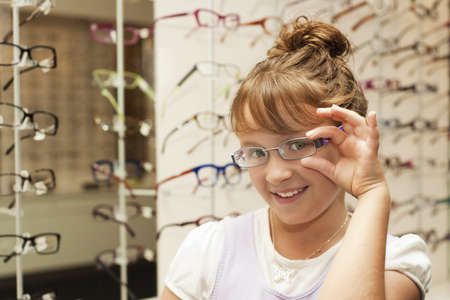 trying: a young girl smiles at her reflection as she tries on new glasses Stock Photo