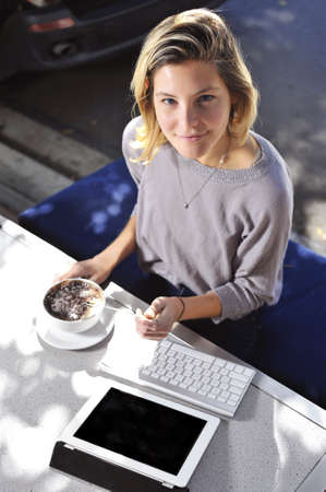 a young woman enjoys her cappucino whilst working photo