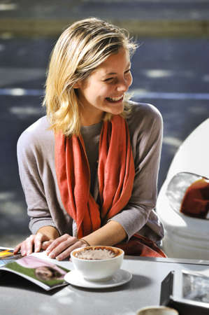 adult magazines: young woman chatting with a friend in a cafe Stock Photo
