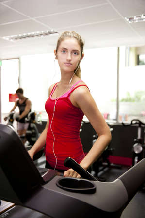 a young woman looks to camera whilst walking on a treadmill in a gym. Stock Photo - 12954163
