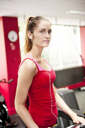 a young woman looks to camera with a semi-serious look as she works out on a treadmill. photo