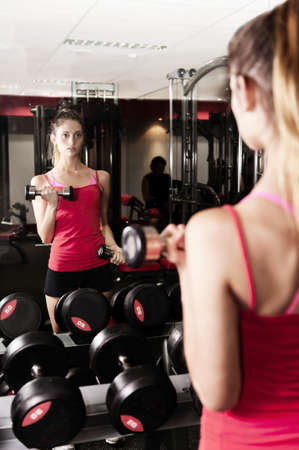 a young woman looks at her reflection as she lifts weights photo