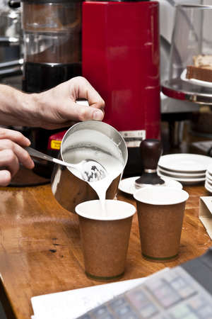 coffees: a barista pours milk to complete the coffee making process. two takeaway coffees. (no brand names on grinder or cups)
