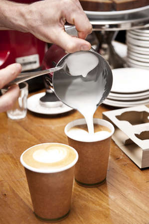 latte art: a barista pours milk to complete the coffee making process, creating a love heart shape in the milk. (no brand names on grinder or cups)