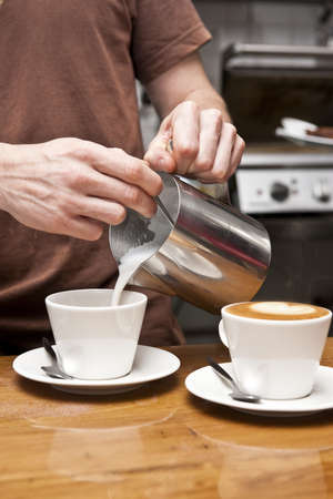 a barista pours milk to complete the coffee making process, this coffee is a