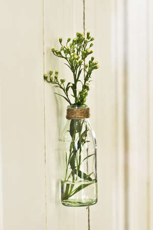 a glass jar is refashioned into a vase for fresh flowers