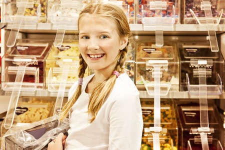 a young girl in a sweet shop, all logos removed