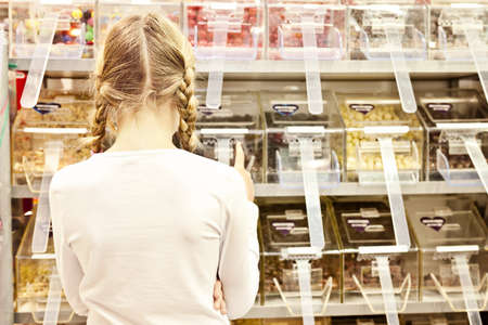 a young girl faces a bay of sweets, all logos removed photo