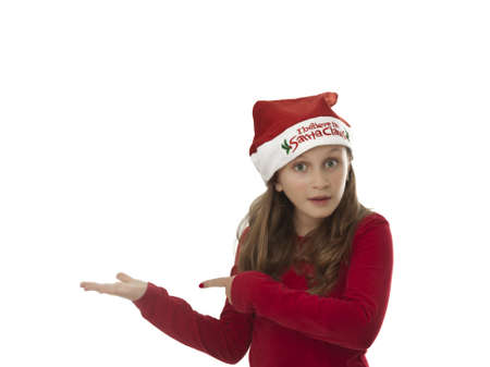 cute young girl with xmas hat pointing to empty hand, insert your object Stock Photo - 16513241