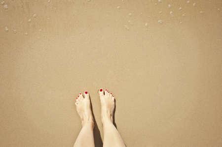 u�as pintadas: los pies en la playa en la orilla del agua