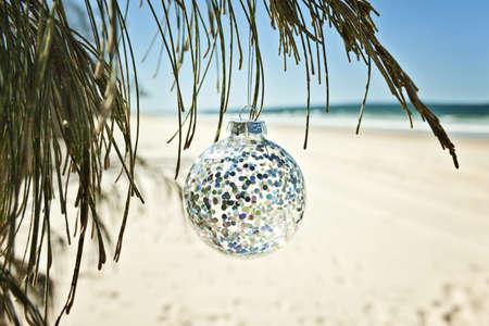 strand australie: een glazen kerstbal hangt aan een boom op het strand Stockfoto