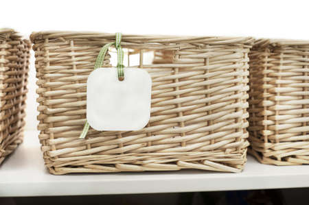 cane baskets on a shelf, white background and blank labelcard with ribbon