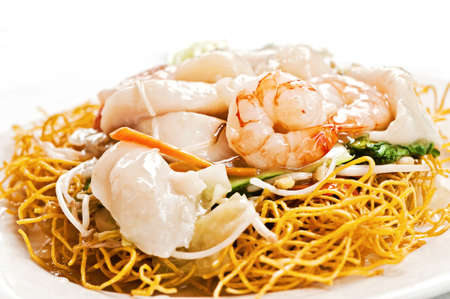 prawns and squid sit atop crunchy fried noodles