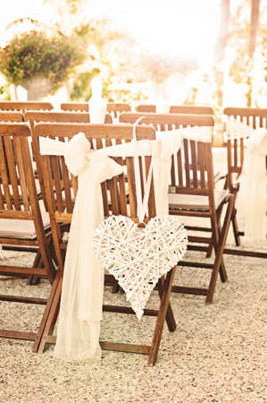wedding chairs: a heart hangs from a chair at a wedding