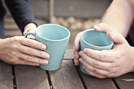 hands holding teacups coffee mugs