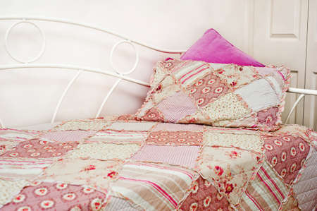 patchwork quilt: pink patchwork quilt on a bed Stock Photo
