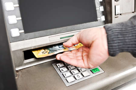 automatic transaction machine: retirar dinero de un cajero autom�tico, recogiendo notas de 50 d�lares australianos