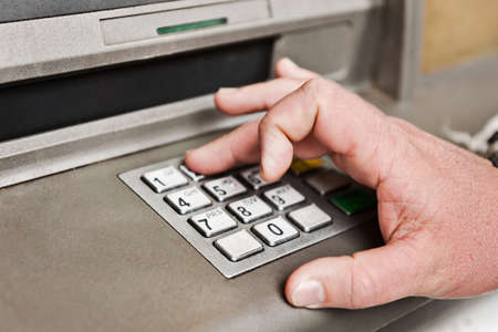 a man enters his pin into the atm.  Stock Photo - 18754516