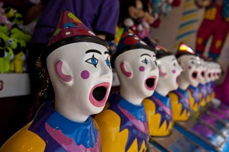 row of clown heads, turning towards camera