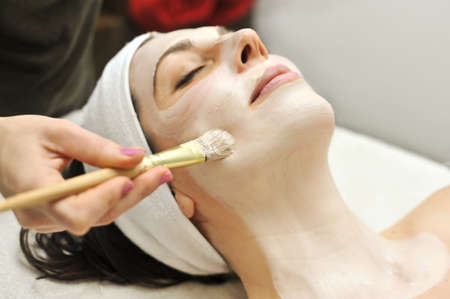 relaxes: a woman relaxes as a beautician applies a fask mask during a beauty treatment