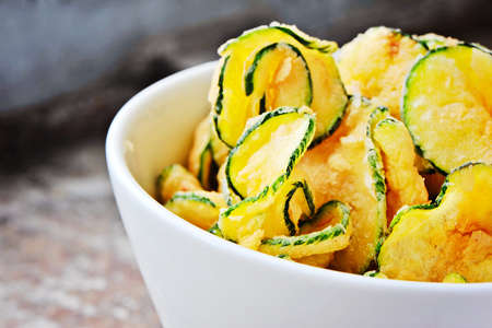 a bowl on zucchini chips, set against an urbanindustrial feel bg