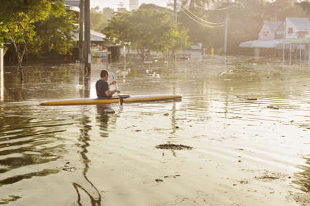 the sun is rising a man uses a canoe to traverse the flooded streets of his local suburb  Brisbane, Australia Great Flood of summer 2011