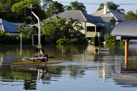 a man uses a canoe to traverse the flooded streets of his local suburb  Brisbane, Australia Great Flood of summer 2011 Stock Photo
