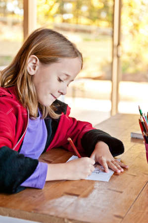 young girl colouring, generic setting could be school, library or home photo