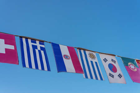 various flags on bunting, against a blue sky photo