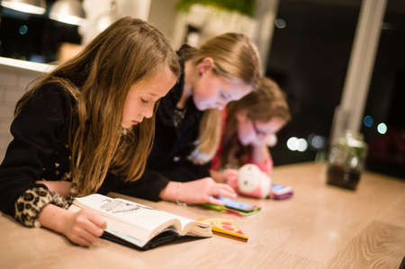 girl reading book while sisters use electronic devices photo