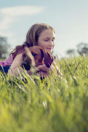 girl in grassy field hugging her pet puppy dog photo
