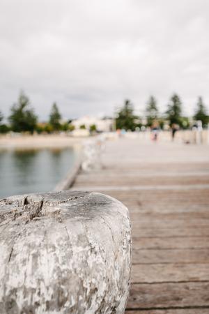 bollard: wooden jetty bollard with blurred people