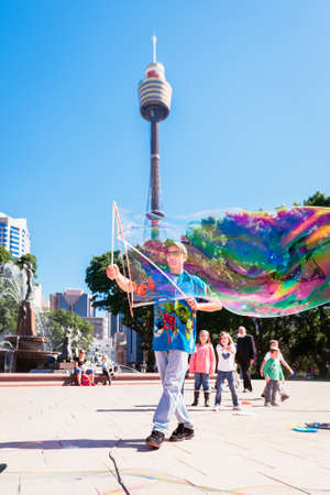 centrepoint tower: street entertainer in Hyde Park, Sydney, Australia, April 2012. the Sydney Tower is visible in the background