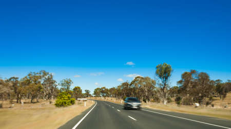 the outback: outback highway with one car zooming towards us Stock Photo