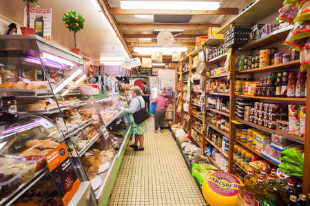 deli: customers shopping in a small, well stocked local deli