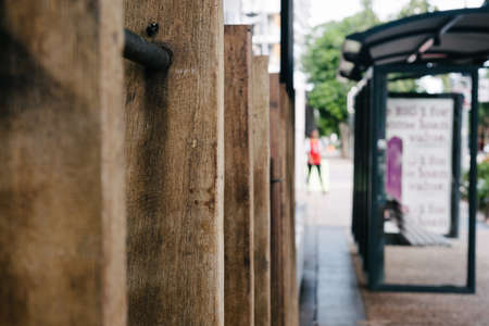 frence: urban street scene, frence, bus shelter and person walking