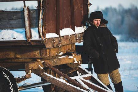 vestidos antiguos: hombre r�stico con ropa vieja al lado de la vieja carrito en el fr�o invierno. Retrato