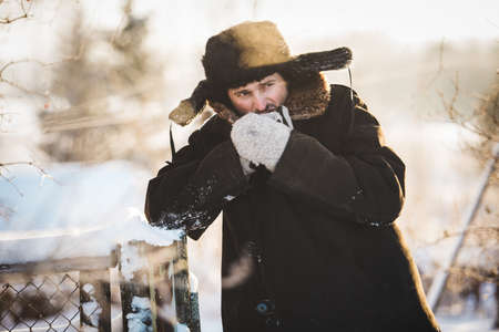 warms: Rustic man in old clothes warms his hands in the cold winter. Portrait