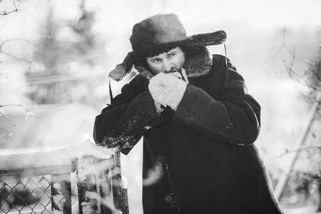 vestidos antiguos: Rustic man in old clothes warms his hands in the cold winter. Black and white portrait Foto de archivo