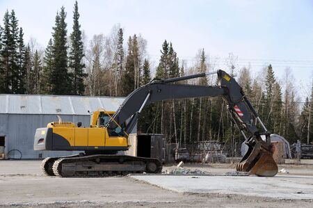 Earthmover sits idle, preparing to rip up old concrete foundation photo