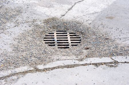 runoff: Gravel covered Storm Drain in an urban roadway