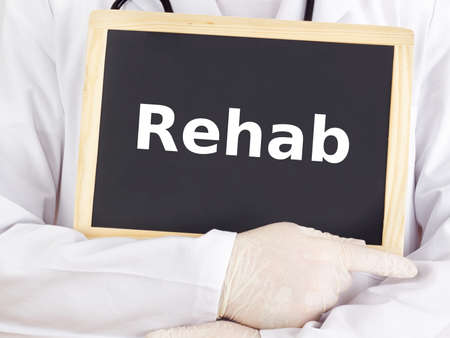 Doctor shows information on blackboard: rehab Stock Photo
